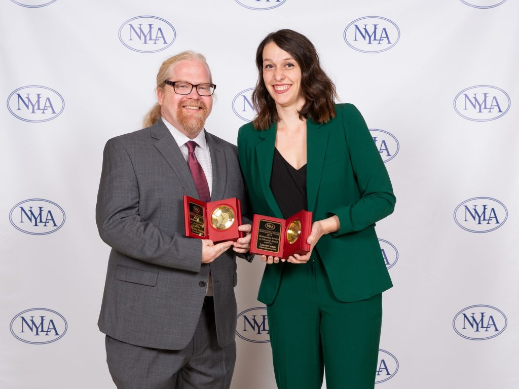 Lauren Comito and Christian Zabriskie  displaying the NYLA Outstanding Service to Libraries Award